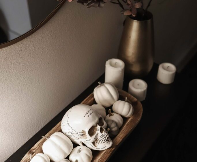 white pumpkins and skull halloween entry table decor